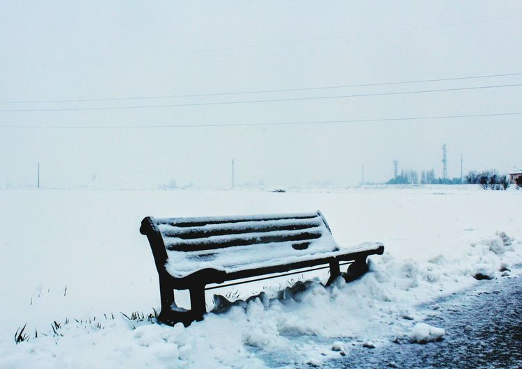 Snow covered empty bench on field