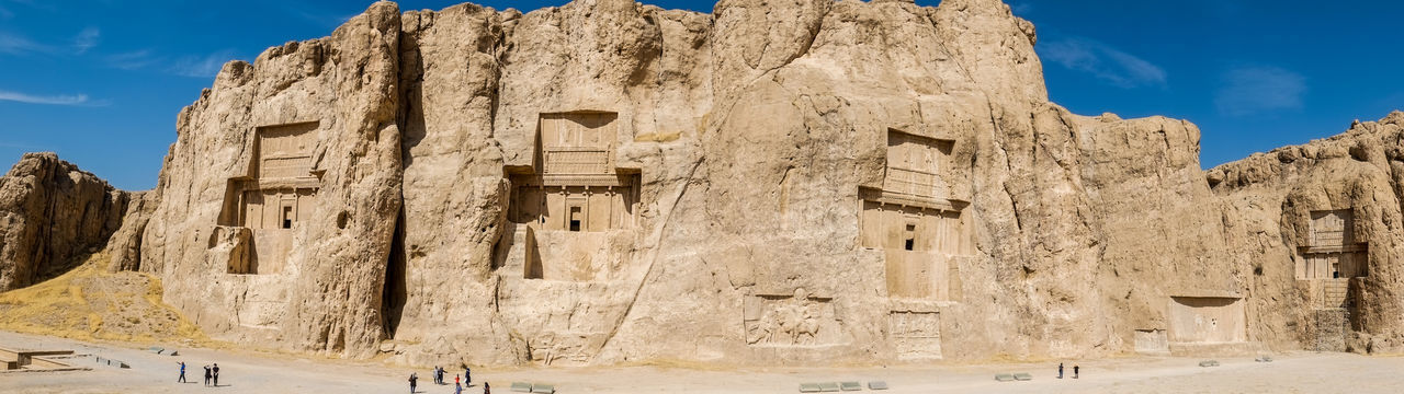 Panoramic view of the naqsh-e rustam shows rock reliefs with four large tombs. fars province, iran.