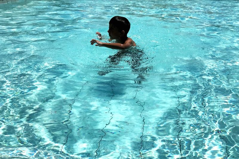 Enjoying The Sun From My Point Of View Water Rippled Textured  Swimming Swimming Pool Summer Summertime Pool Water Swimming Pool One Person Waterfront Leisure Activity Real People Lifestyles Swimming Child Boys Childhood Turquoise Colored Human Arm Blue Day Outdoors