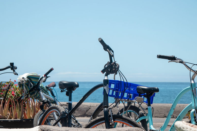 Bicycle parked by sea against clear blue sky