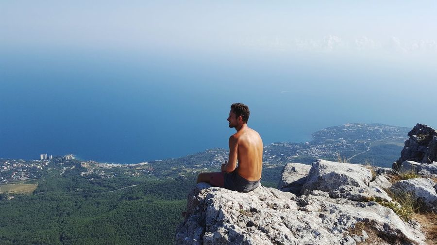 Shirtless man looking at sea while sitting on cliff during sunny day