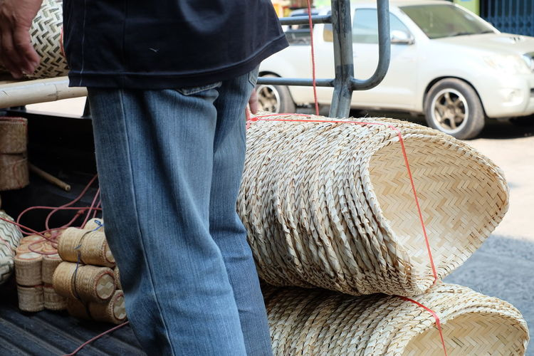 Midsection Of Man Loading Wicker Baskets On Vehicle