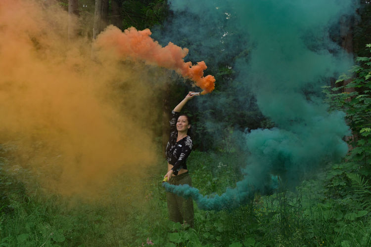 Woman standing by color smoke in forest