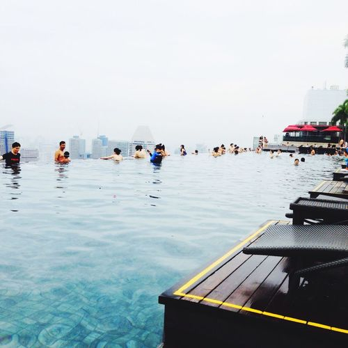 People enjoying in swimming pool at marina bay sands against clear sky