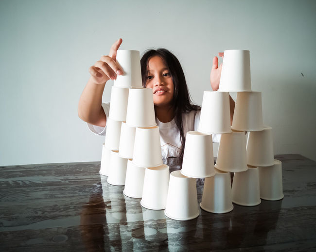 Smiling girl stacking glasses on table