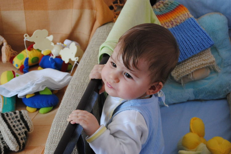 Cute boy with toys in crib