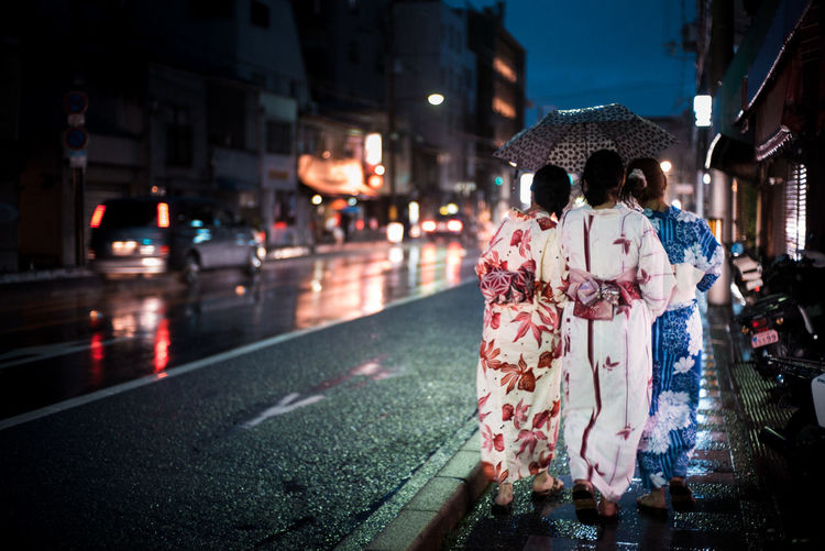 Rear View Of Women Wearing Kimonos Walking On Street At Night