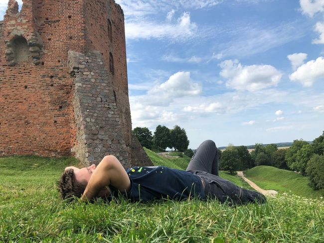 EyeEm Selects Relaxation One Person Lying Down Sky Plant Leisure Activity Full Length Casual Clothing Low Section Nature Resting Women Cloud - Sky Real People Lifestyles Adult Sunlight Body Part Day Grass