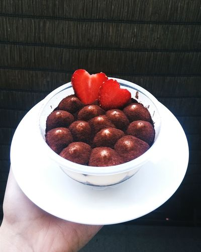 Close-up of hand holding strawberries in bowl