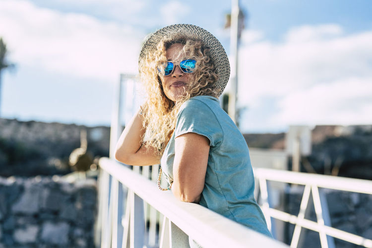 Portrait of boy wearing sunglasses standing against railing
