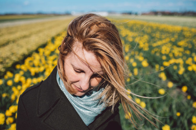 Portrait of woman with yellow flowers on field