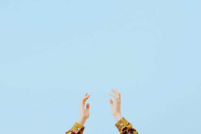 Cropped hands against clear blue sky