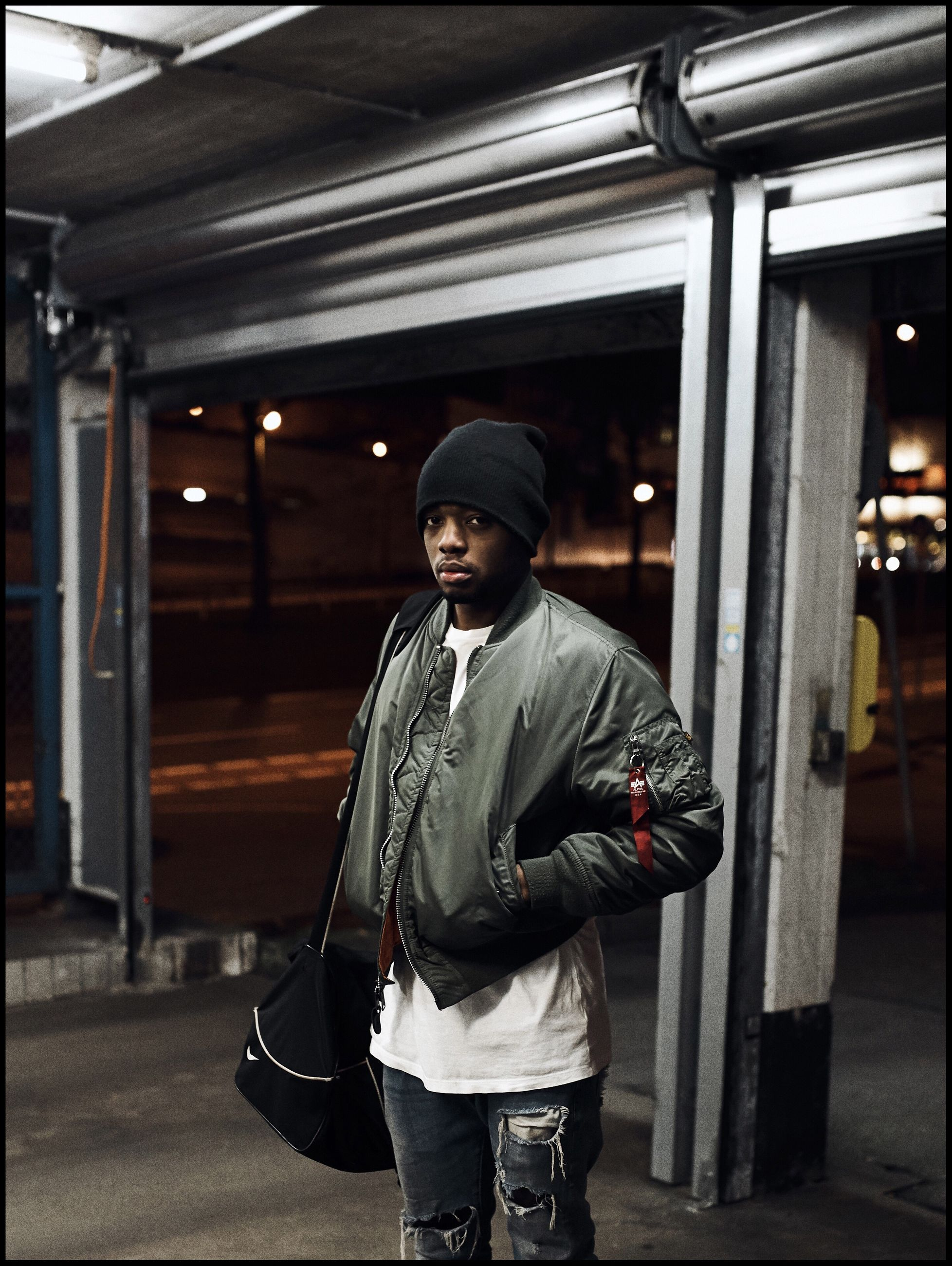real people, one person, front view, lifestyles, young adult, leisure activity, jacket, young men, casual clothing, standing, full length, hooded shirt, men, outdoors, illuminated, night, warm clothing, people