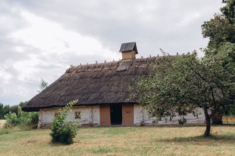 Old house on field against sky