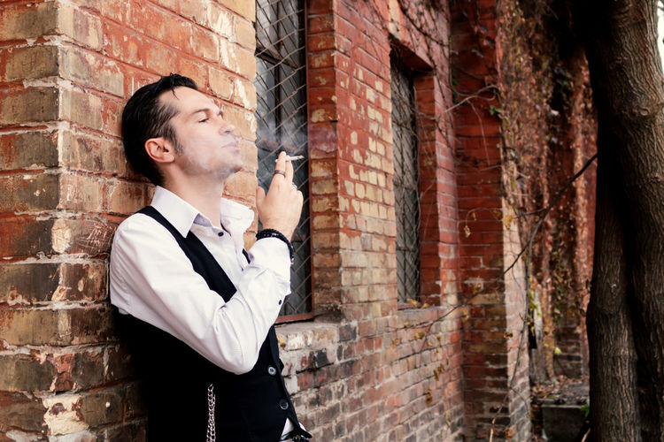 Young man looking away against brick wall