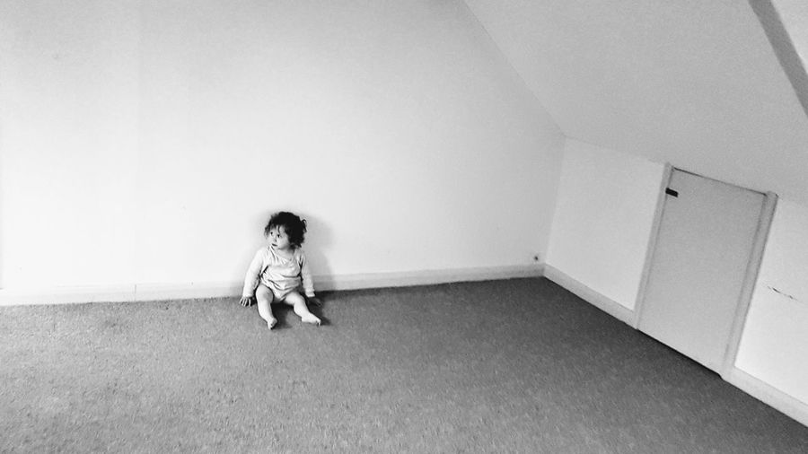 High angle view of girl looking away while sitting on floor at home