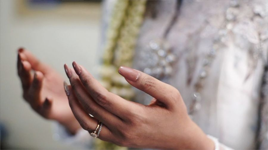 Midsection of woman gesturing while praying