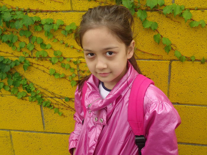 Architecture Building Exterior Built Structure Casual Clothing Childhood Close-up Cute Day Elementary Age Front View Girls Happiness Leisure Activity Lifestyles Looking At Camera One Person Outdoors Pink Color Portrait Real People Smiling Standing Wall - Building Feature Yellow