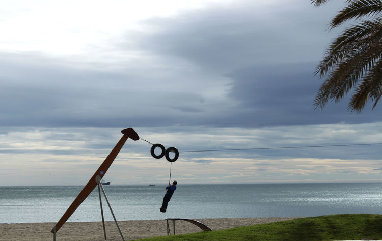 a boy is playing at the coast in Malaga, Spain Beach Blue Boy Calm Cloud - Sky Coastline Horizon Over Water Idyllic Joy Malaga Nature Ocean Outdoors Palme Playground Playing Sea Seilbahn Silhouette Sky Spielen Swing Tranquility Vacations Water