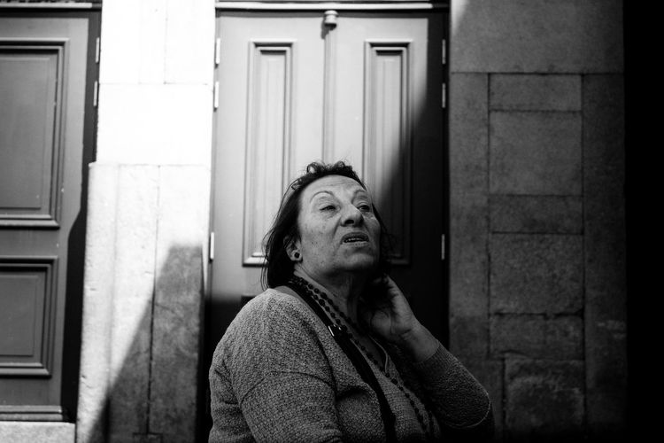 Thoughtful Senior Woman Against Closed Door