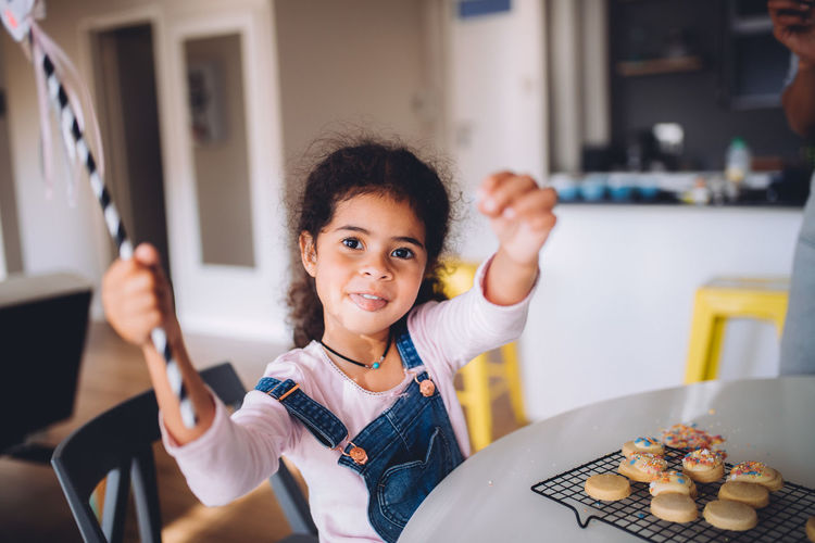 Portrait of smiling girl with cookies on table gesturing at home