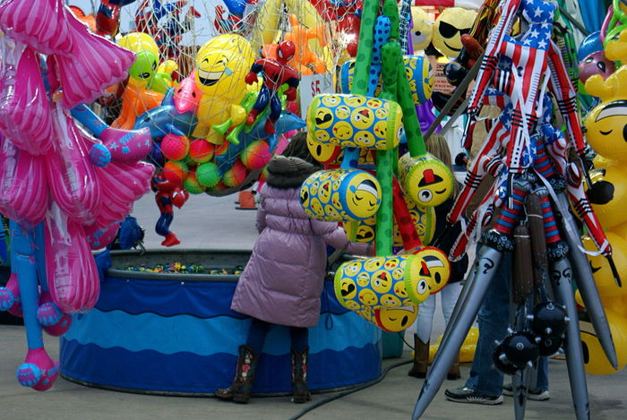 Lots of brightly colored balloons and plastic toys, and the back of a girl in a purple winter coat, choosing her duck, at a carnival midway. Brightly Colored Carnival Day Festive Fun Game Inflatables Leisure Activity Midway Multi Colored Outdoors Prizes Toys