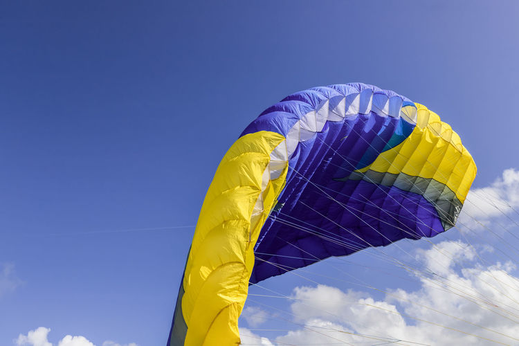 Low angle view of parachute against blue sky