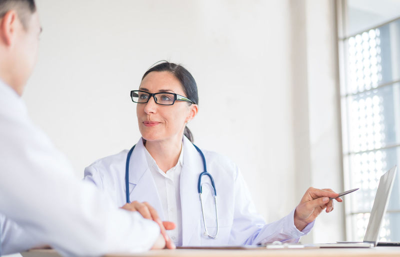 Female doctor explaining patient over laptop at table in clinic