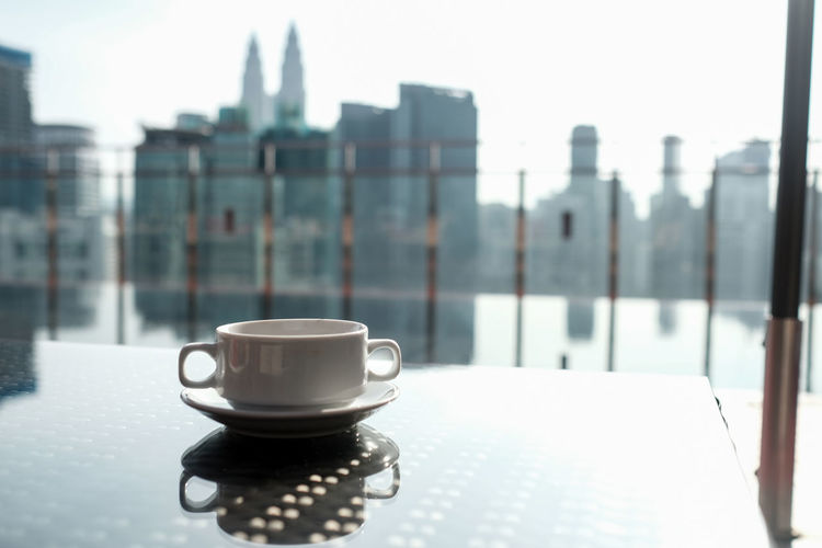 Coffee cup on window in city
