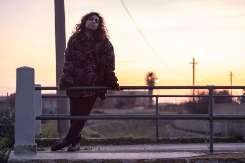 Portrait of man standing on bridge against sky during sunset
