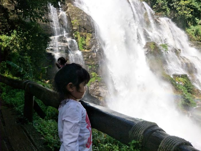 Girl standing against waterfall
