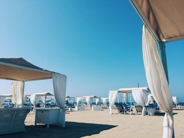Covered tables and chairs at beach against clear blue sky