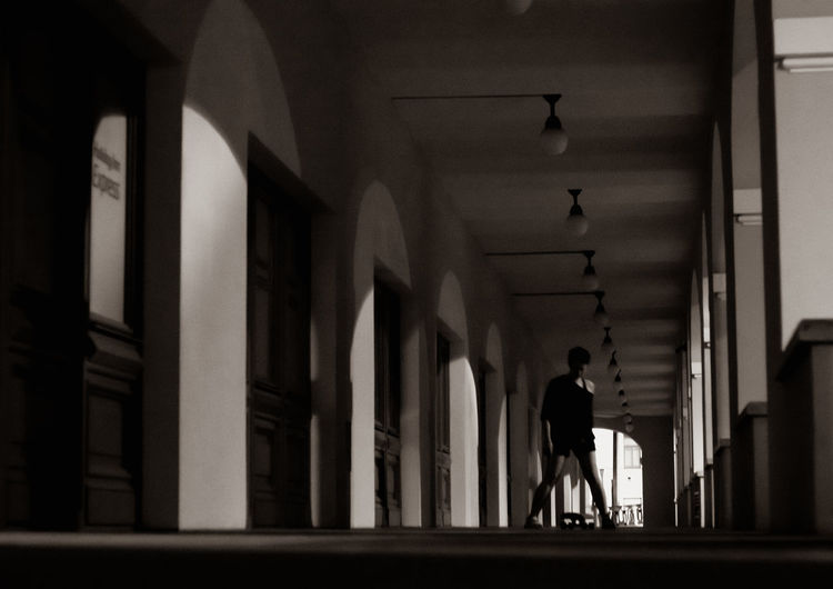 Rear view of silhouette man walking in corridor of building