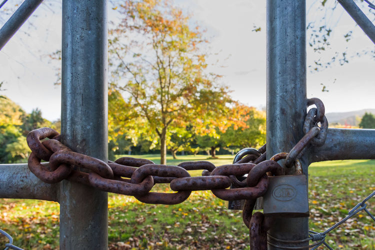 Close-up of rusty chain against fence