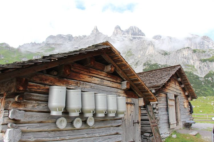 Milk canisters on wooden cottage