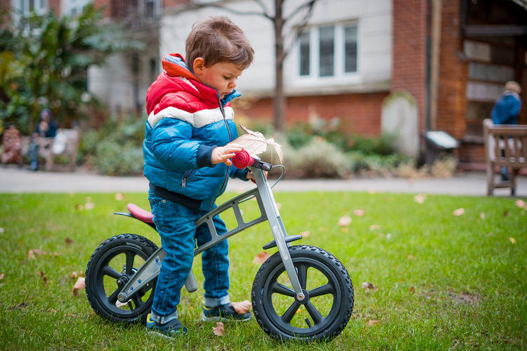 Boy playing with bicycle in grass