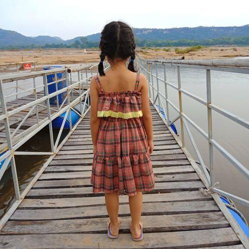Rear view of girl standing on footbridge over sea