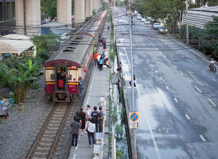 BANGKOK, THAILAND. – On September 27, 2018. – Diesel Train is stopping at a platform with passengers, at Makkasan station. Transportation Mode Of Transportation High Angle View Group Of People City Street Road Real People Architecture Large Group Of People Outdoors Crowd Bangkok Thailand Urban Life Style Vintage Train Railway Track Editorial Photography Platform Stoping Passenger Traveling