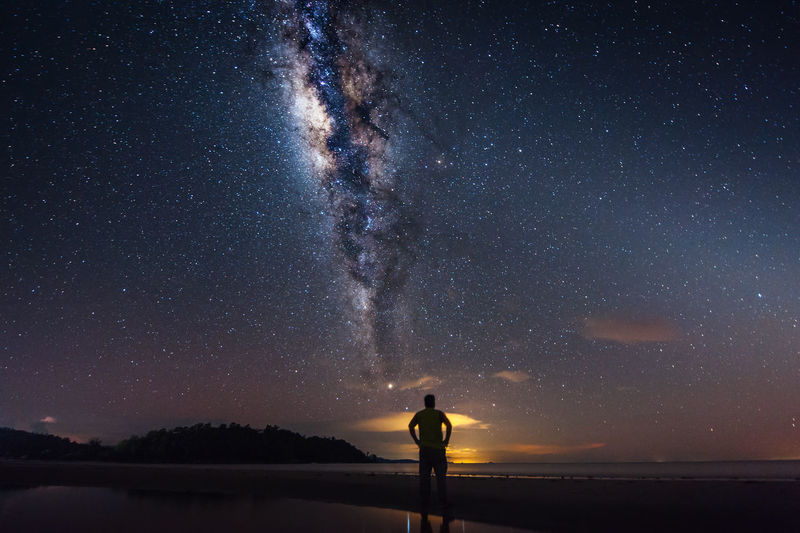 Rear view of man standing on shore while looking at milky way in sky