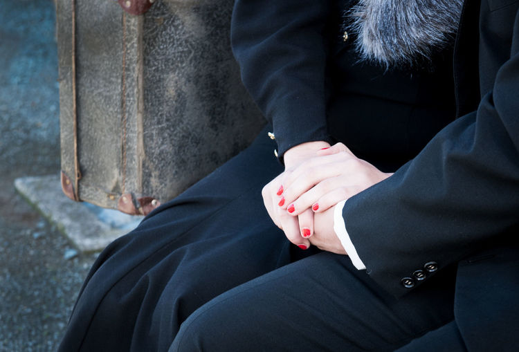 Midsection Of Couple In Suit Sitting Outdoors