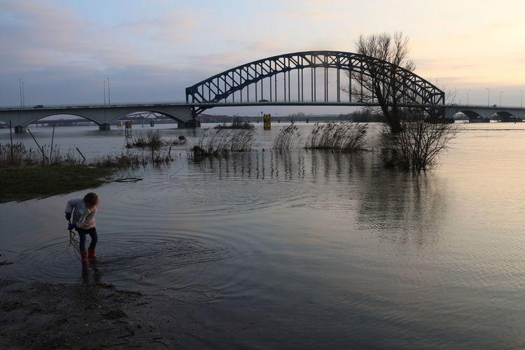 Girl standing in river against bridge during sunset