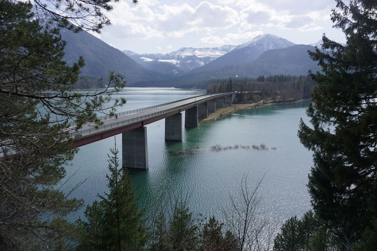 Scenic view of lake and mountains against sky with bridge