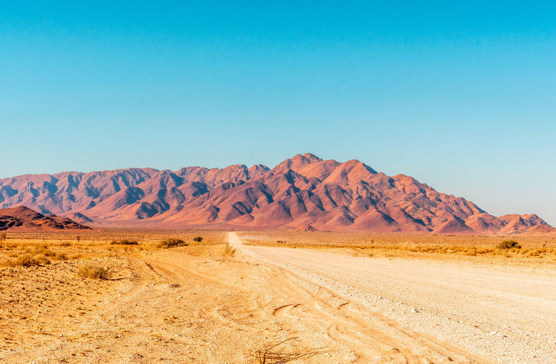 Scenic view of desert landscape against clear blue sky