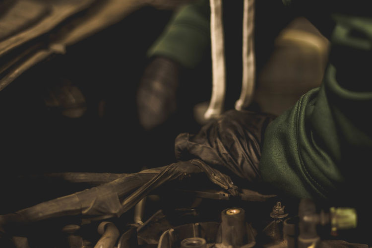 Mechanic working in SUV engine compartment, preparing to pull engine. Automobile Dark Engine Compartment Forearms Green Mechanic SUV Work Working Auto Black Car Close-up Dirty Engine Fingers Gloves Hand Handsome Labor Mechanic Shop Mechanic Working Shop Sleeves Wrists