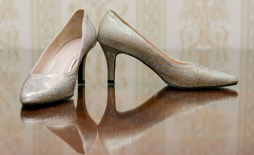 Silver high heels on glass table with reflection