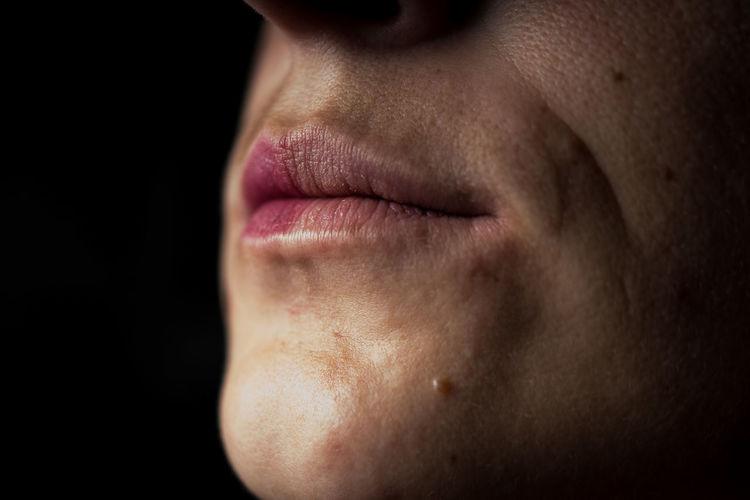 Close-up of man wearing lipstick in darkroom