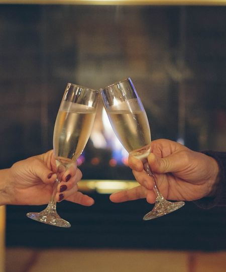 Man and woman's hands holding a glass of champagne in a toast by the fireplace celebrating and romantic Love Anniversary Romantic Human Hand Hand Human Body Part Celebratory Toast Alcohol Holding Indoors  Celebration Drink Adult Champagne Food And Drink Refreshment Wine Champagne Flute Women Two People Glass Close-up People