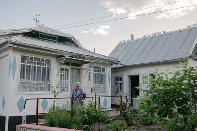 Woman standing outside house