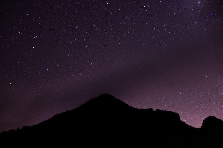 Low angle view of silhouette mountain against sky at night with stars