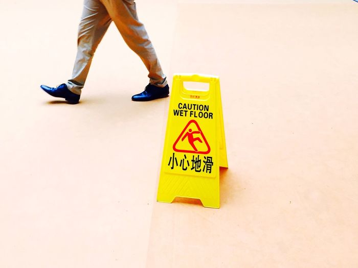 Low section of man walking by caution wet floor sign